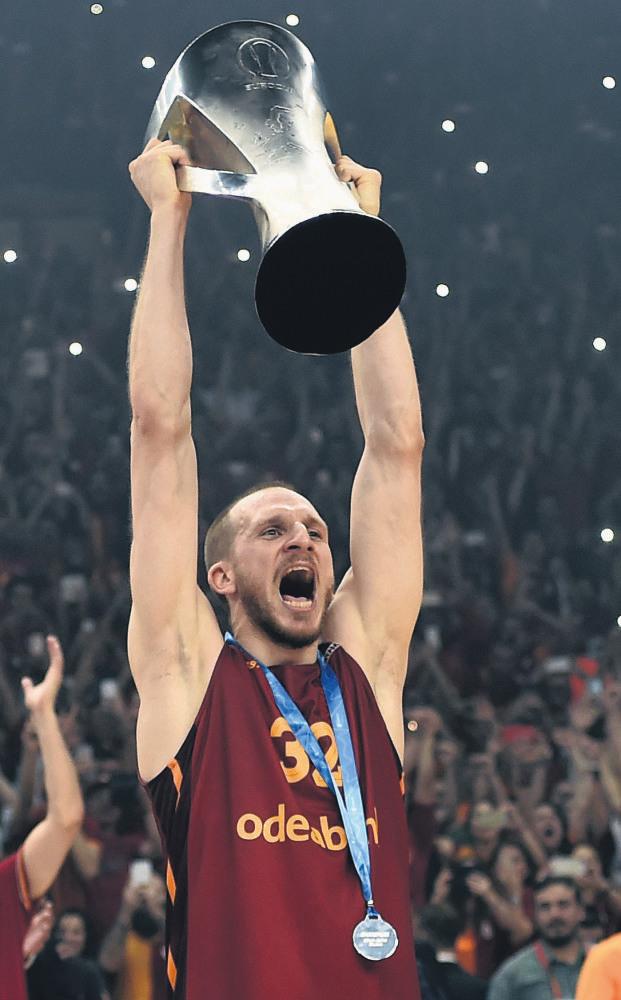 Galatasaray guard Sinan Güler holds up the Eurocup trophy.