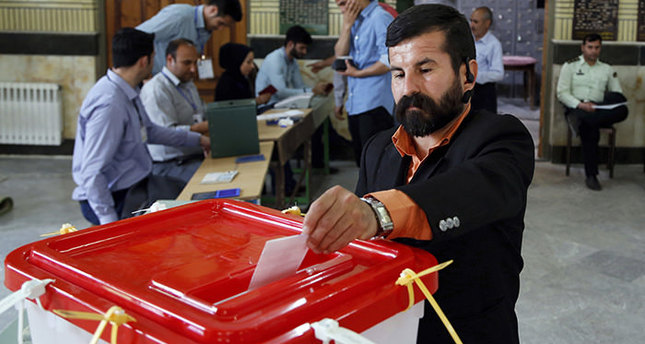 An Iranian voter casts his ballot for the parliamentary runoff elections in a polling station at the city of Qods about 12 miles (20 kilometers) west of the capital Tehran, Iran, Friday, April 29, 2016 (AP Photo)