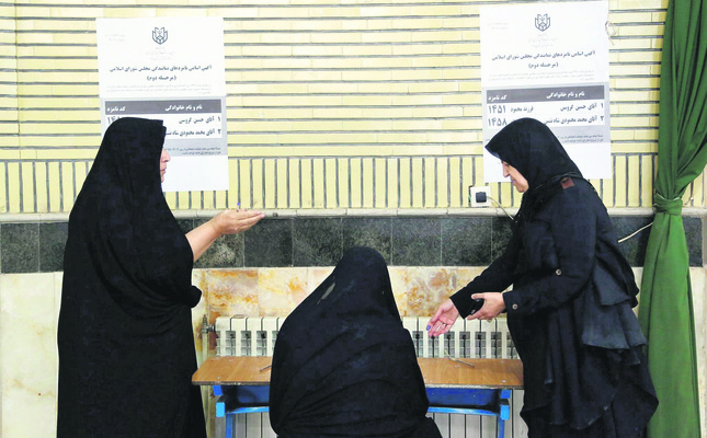 Iranian women fill their ballot to vote in a polling station during the second round of parliamentary elections. (EPA Photo)