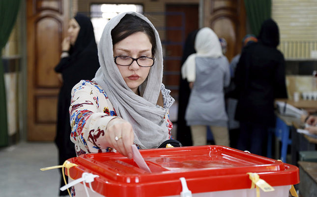 An Iranian woman casts her ballot for the parliamentary runoff elections in a polling station at the city of Qods about 12 miles (20 kilometers) west of the capital Tehran, Iran, Friday, April 29, 2016. (AP Photo)