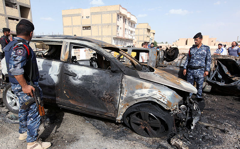 Policemen gather at the site of a car bomb attack in Samawa, south of Baghdad, May 1, 2016. (Reuters)