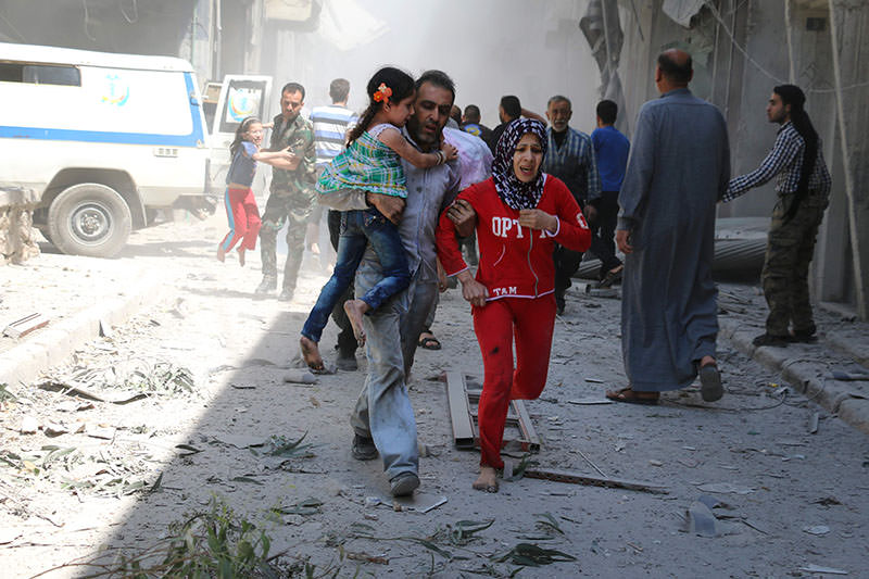 Syrian family runs for cover amid rubble of destroyed buildings in northern Syrian city of Aleppo, on April 29, 2016 (AFP)