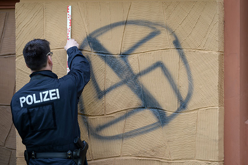 A policeman securing evidence of a crossed swastika sprayed on the facade of the house of AfD party deputy Alexander Gauland in Potsdam, Germany, 26 April 2016. (EPA)
