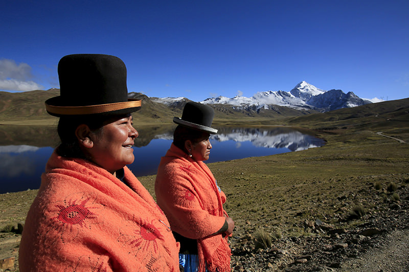 Aymara indigenous women Lidia Huayllas, 48, (L) and Dora Magueno, 50, stand near Milluni lake, with the Huayna Potosi mountain in the background. (REUTERS Photo)