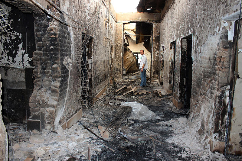 In this Oct. 16, 2015, file photo, an employee of Doctors Without Borders stands inside the charred remains of their hospital after it was hit by a U.S. airstrike. (AP Photo)
