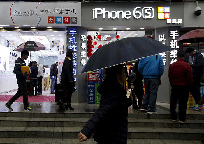 People walk past stores promoting the Apple iPhone 6S in the southern city of Shenzhen, China January 26, 2016 (Reuters Photo)