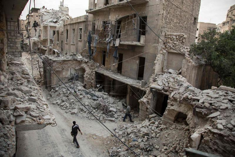 A man walking amid destroyed buildings in Aleppo's Bab al-Hadid neighbourhood, Syria.