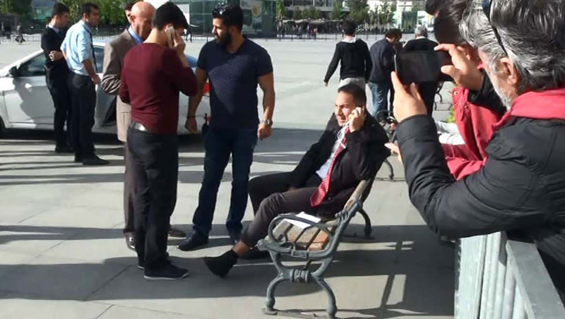 NTV reporter Şenkal (sitting on the bench) continued reporting the incident in live broadcast only minutes after he was injured from his right leg. (DHA)