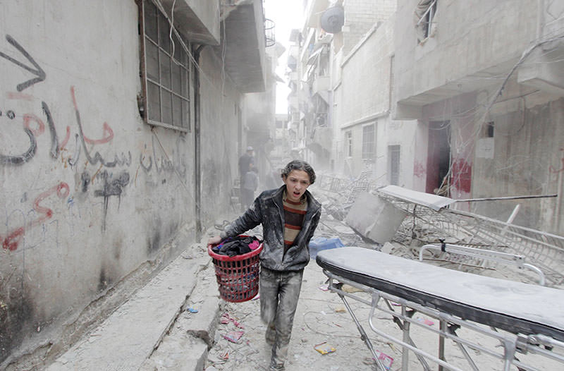 A boy carries his belongings at a site hit by what activists said was a barrel bomb dropped by forces loyal to Bashar al-Assad in Aleppo, April 2, 2015. (Reuters)