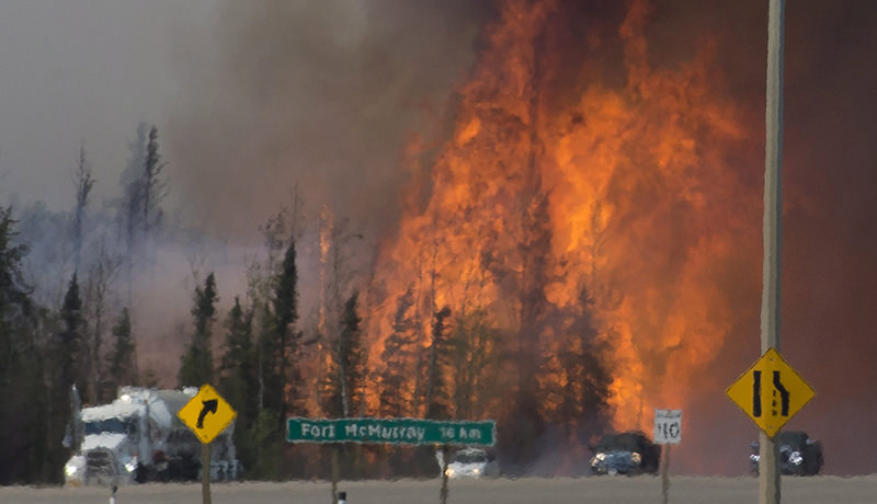 Heat waves are seen as cars and trucks try and get past a wild fire 16 km south of Fort McMurray, Alberta, on highway 63, Friday, May 6, 2016 (AP Photo)