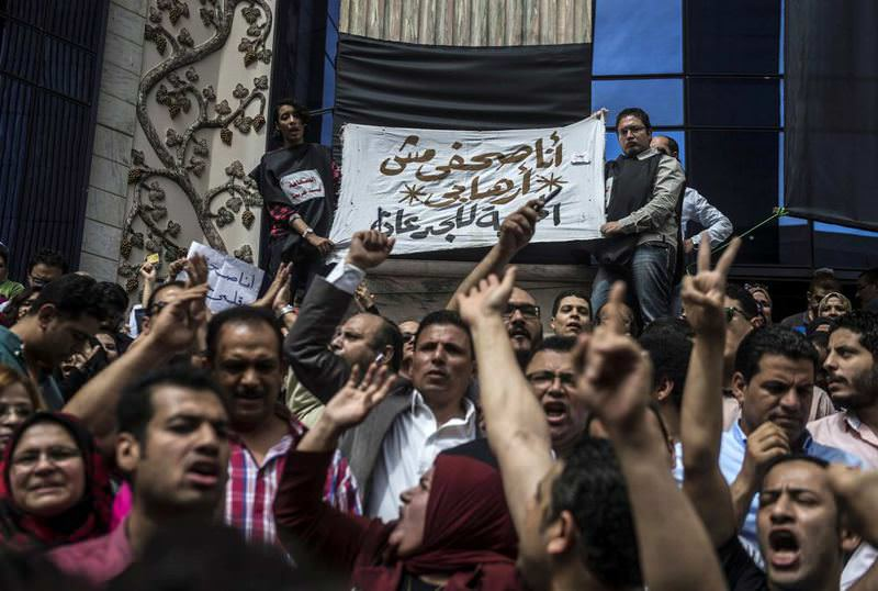 Journalists hold a banner in Arabic that reads: ,I am a journalist not a terrorist,, during a demonstration outside the Journalist Syndicate headquarters in Cairo.