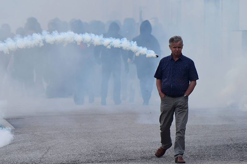 A man walks along a street as a smoke bomb is thrown during clashes between 'No border' activists andItalian police at the Brenner train station on May 7, 2016. (AFP Photo)
