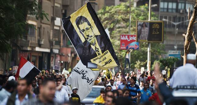 Supporters of the Muslim Brotherhood and ousted president Mohamed Morsi hold up his image as they take part in a march through the streets of Cairo in his support on November 8, 2013. (AFP Photo)