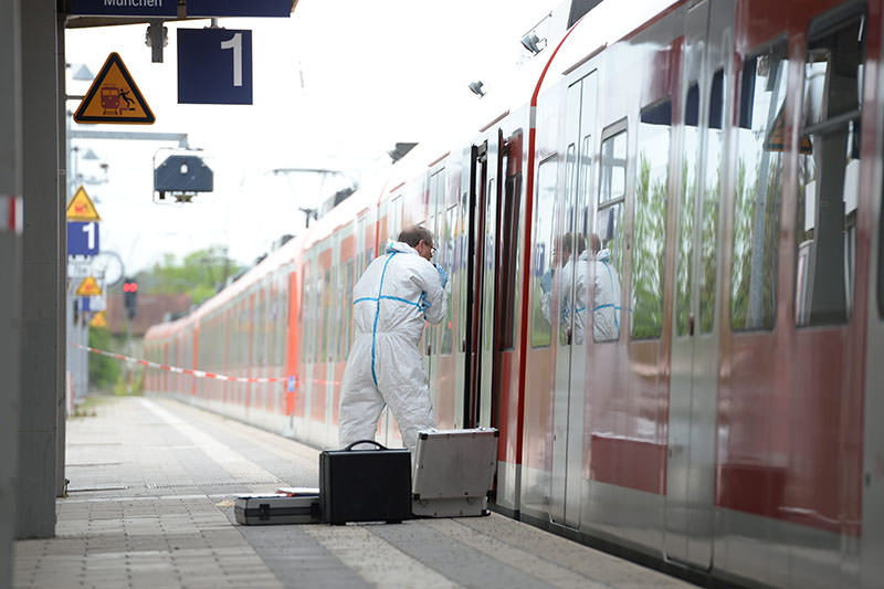 A forensic investigator of the German police next to a local train at the railway station in Grafing near Munich, Germany, 10 May 2016 (EPA)
