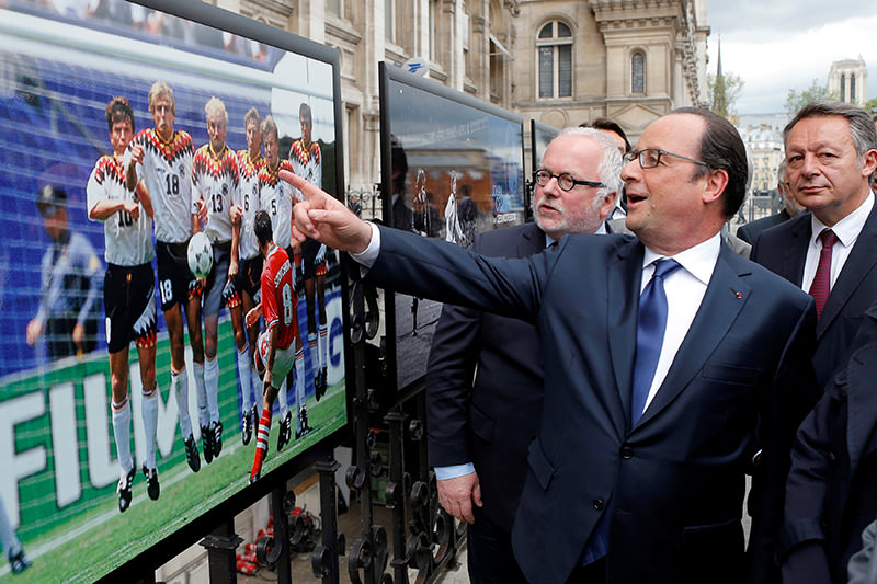 French President Francois Hollande (2ndL), flanked with French Soccer specialist Pierre Louis Basse (L), comment on a photo of Bulgarian soccer player Hristo Stoitchkov (Reuters Photo)