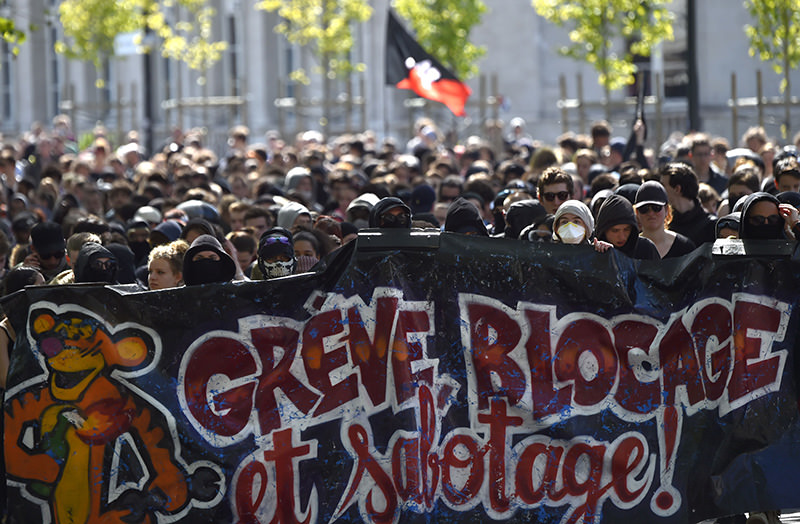 People hold a banner reading ,Strike, blockade and sabotage, as they march during a protest against the government's planned labour law reforms in Nantes, western France, on May 3, 2016. (AFP Photo)