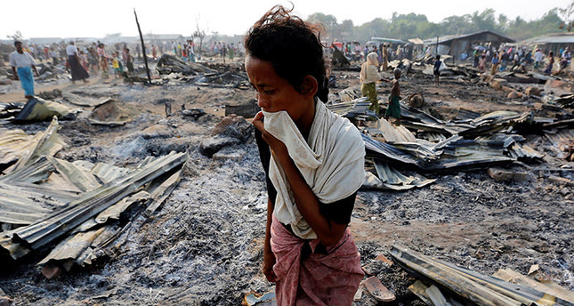 A woman walks among debris after fire destroyed shelters at a camp for internally displaced Rohingya Muslims in the western Rakhine State near Sittwe. (REUTERS Photo)