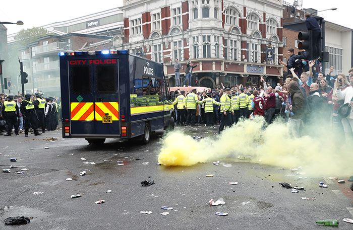 General view of a smoke bomb among police and fans before the match (Reuters Photo)