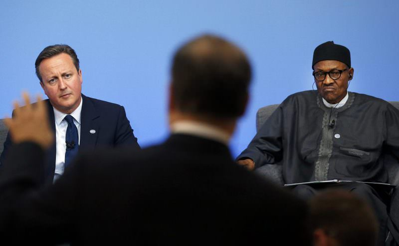British Prime Minister David Cameron (L) and Nigerian President Muhammadu Buhari listen during a panel discussion at the Anti-Corruption Summit in London on Thursday. (Reuters Photo)