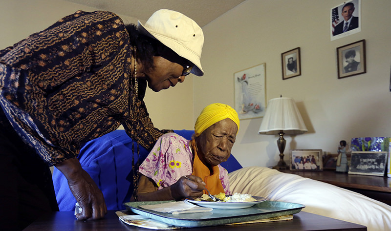 In this Monday, June 22, 2015 photo, Lois Judge, left, helps her aunt Susannah Mushatt Jones, during breakfast in Jones' room at the Vandalia Avenue Houses, in the Brooklyn borough of New York (AP Photo)