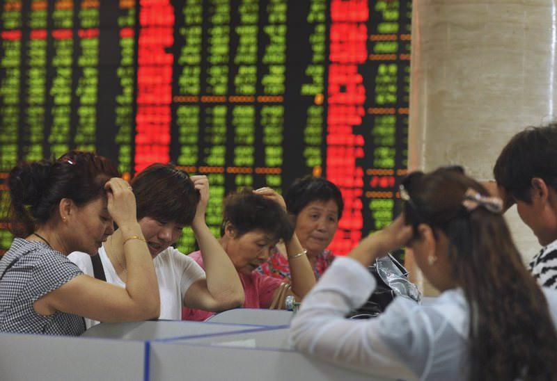 Investors react as they look at computer screens showing stock information at a brokerage house in Fuyang, China.
