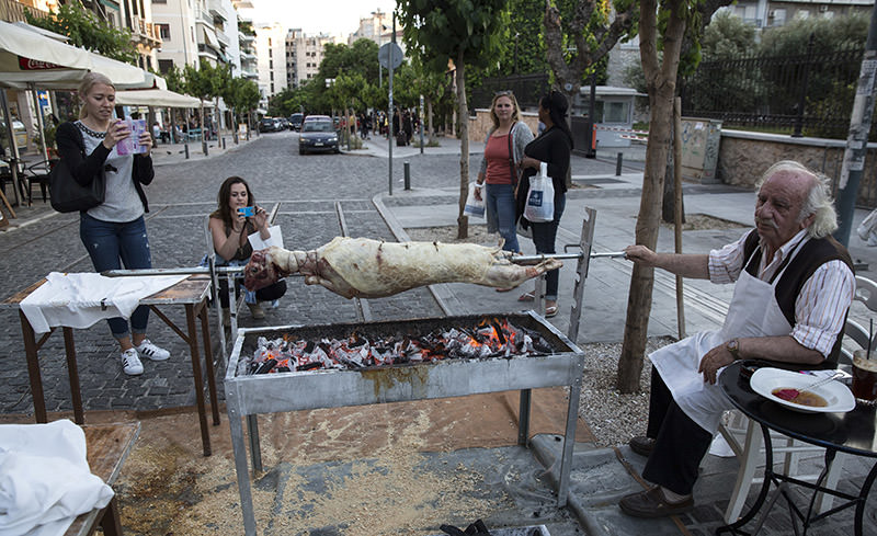 Tourists take photographs of a man who grills a lamb outside a restaurant in Athens, on Saturday, April 30, 2016 (AP Photo)