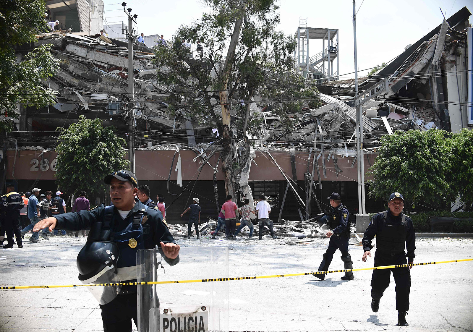 Police officers cordon the area off after a building collapsed during a quake in Mexico City on September 19, 2017. (AFP Photo)