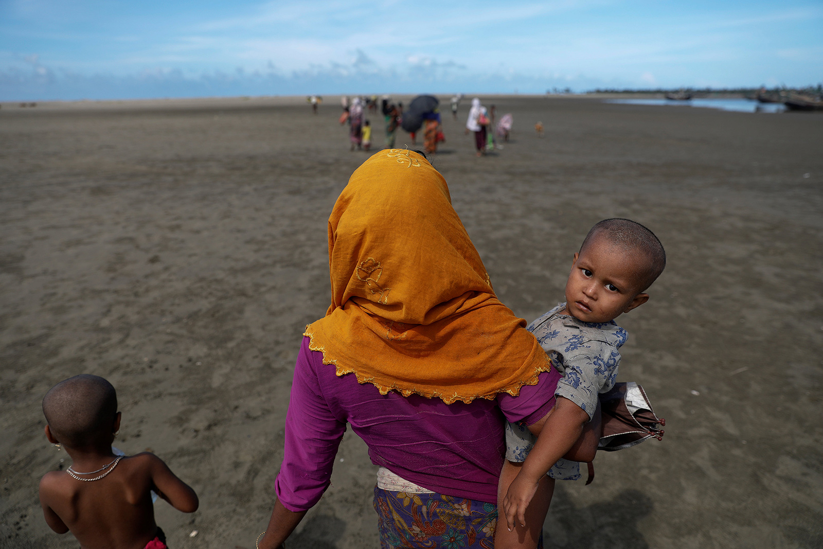 Rohingya refugees who just arrived by a wooden boat from Myanmar carry their children and belongings as they walk toward Shah Porir Dwip, in Teknaf, near Cox's Bazar in Bangladesh, October 1, 2017 (Reuters Photo)
