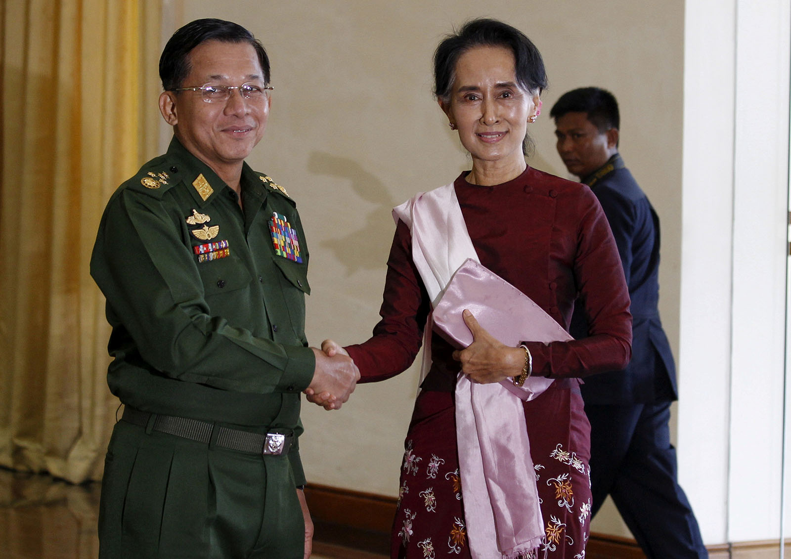 Senior General Min Aung Hlaing (L), Myanmar's commander-in-chief, shakes hands with National League for Democracy (NLD) party leader Aung San Suu Kyi before their meeting in Hlaing's office at Naypyitaw December 2, 2015.