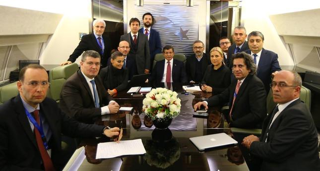 رئيس الوزراء التركي احمد داود أوغلو، مع عدد من الصحفيين أثناء عودته من آذربيجان الى أنقرة  (وكالة الأناضول للأنباء)
