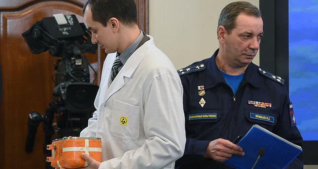 خبير روسي أثناء محاولة فتح الصندوق الأسود للمقاتلة الروسية التي أسقطتها تركيا   (وكالة الأنباء الفرنسية)