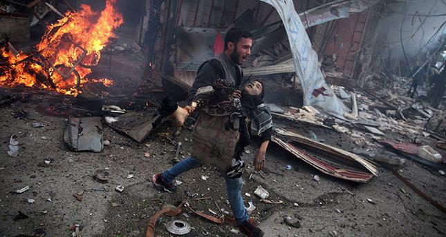 مواطن سوري يحمل جثة طفل قتلته صائرات النظام في قصف على مدينة دوما غربي دمشق 27 نوفمبر 2015  وكالة الأنباء الفرنسية