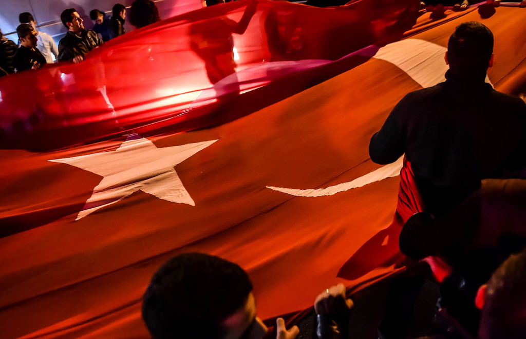 People hold a giant Turkish national flag during a demonstration on December 11, 2016 a day after twin bombings near the home stadium of Besiktas football club. (AFP Photo)