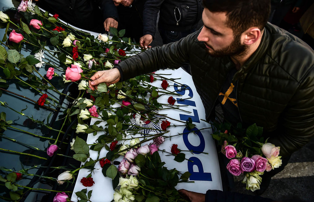A man lays flowers on a police vehicle as people pay their respects outside the Vodafone Arena football stadium in Istanbul on December 11, 2016 (AFP Photo)