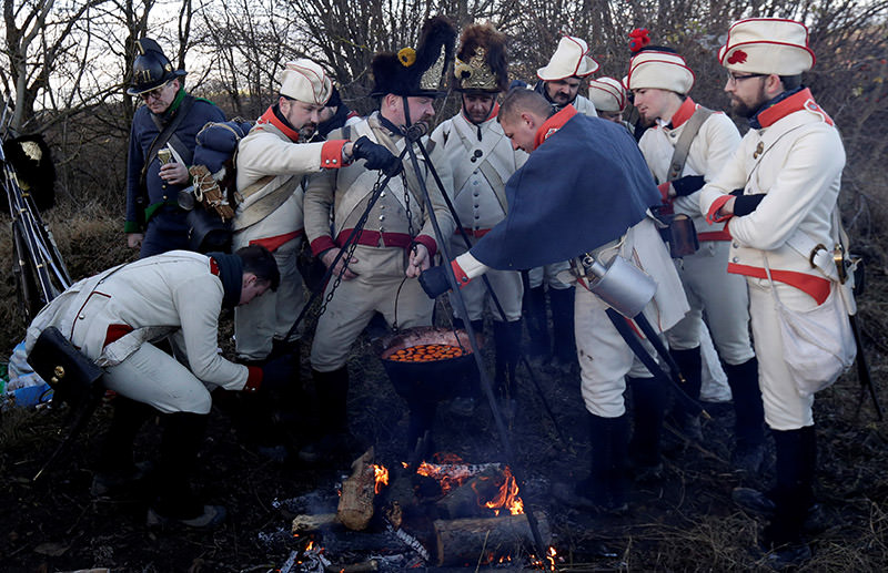 Historical re-enactment enthusiasts dressed as soldiers cook ahead of a re-enactment of battle of Austerlitz. (Reuters Photo)