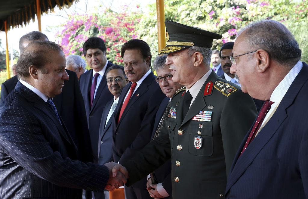 Pakistan's Prime Minister Nawaz Sharif, left, shake hands with Turkish Chief of Staff Gen. Hulusi Akar during a ceremony for President Recep Tayyip Erdoğan, in Islamabad, Pakistan. (AP Photo)