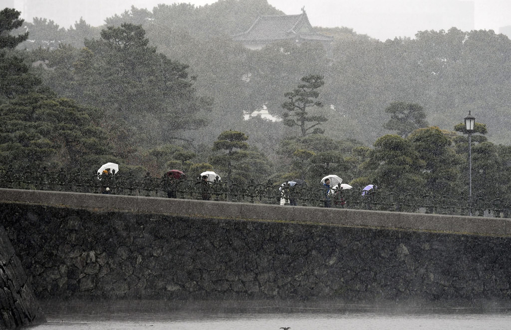 Tourists visit the surrounding gardens of the Imperial Palace during snowfall in Tokyo, Japan, 24 Nov. 2016. (EPA Photo)