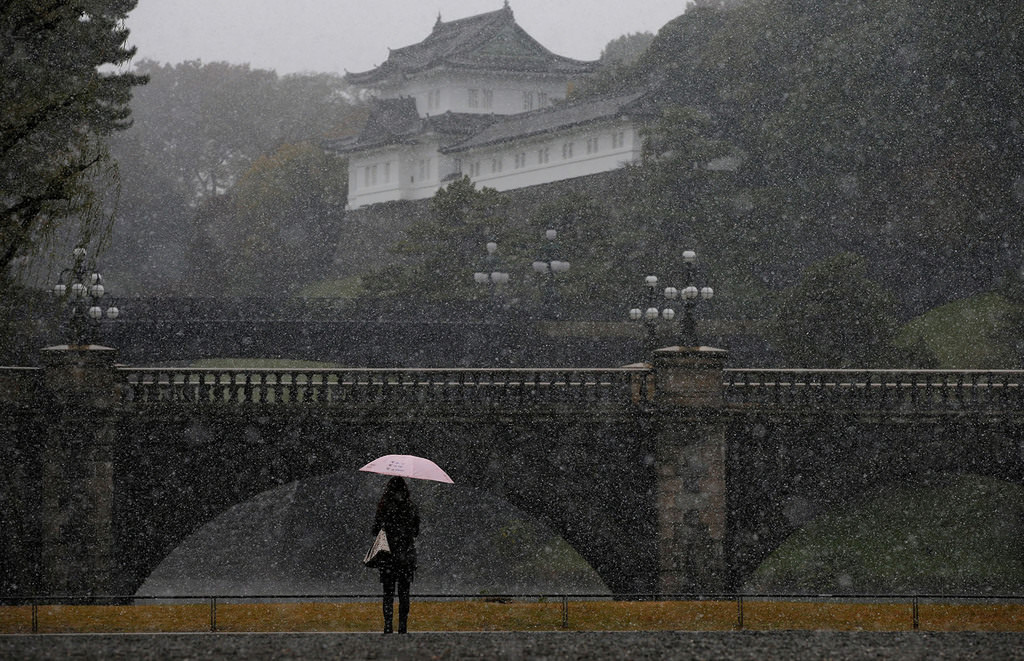 A tourist is seen during the first November snowfall in 54 years in Tokyo, at the Imperial Palace in Tokyo, Japan, Nov. 24, 2016. (REUTERS Photo)