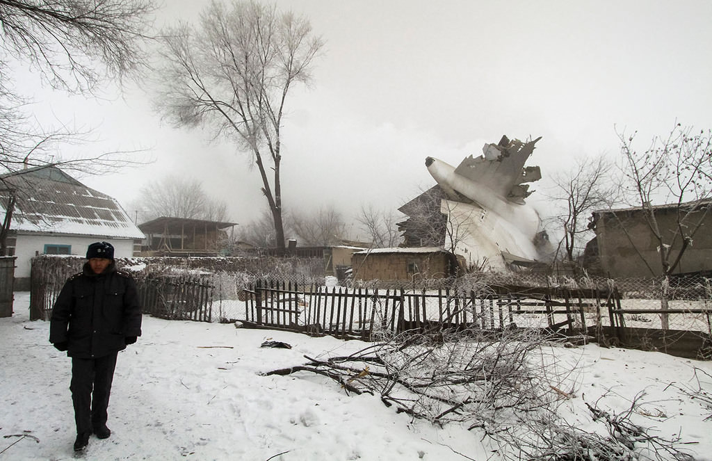 A policeman guards an area at the crash site of a Turkish cargo jet near Kyrgyzstan's Manas airport outside Bishkek, January 16, 2017. (Reuters Photo)