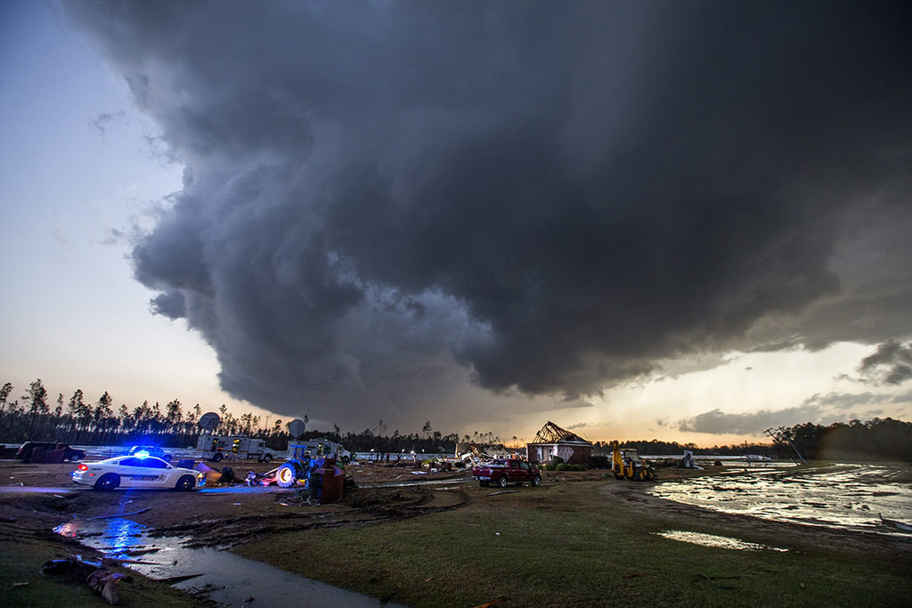 Storm clouds approach emergency crews at the scene of a house cut in half by a tornado near where seven people were killed outside Adel, Georgia USA on 22 January 2017 (EPA Photo)