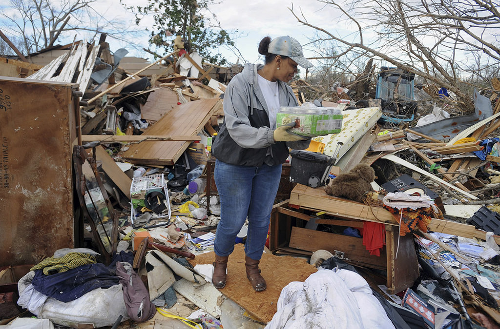 A volunteer helps salvage a Hall Avenue resident's personal belongings as cleanup continued in neighborhoods destroyed by Saturday's twister Sunday, Jan. 22, 2017. (AP Photo)