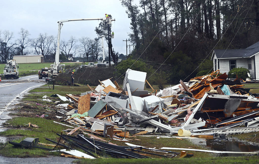 The remains of a house sit in a debris pile along Highway 122 as power line workers repair a downed line Sunday, Jan. 22, 2017, near Barney, Ga. (AP Photo)