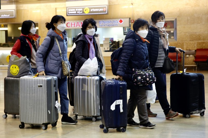 Tourists from Korea wearing protective masks walking with their belongings while waiting for a flight back to South Korea at the Ben Gurion airport near Tel Aviv, Israel, Monday, Feb. 24, 2020. (AP Photo)