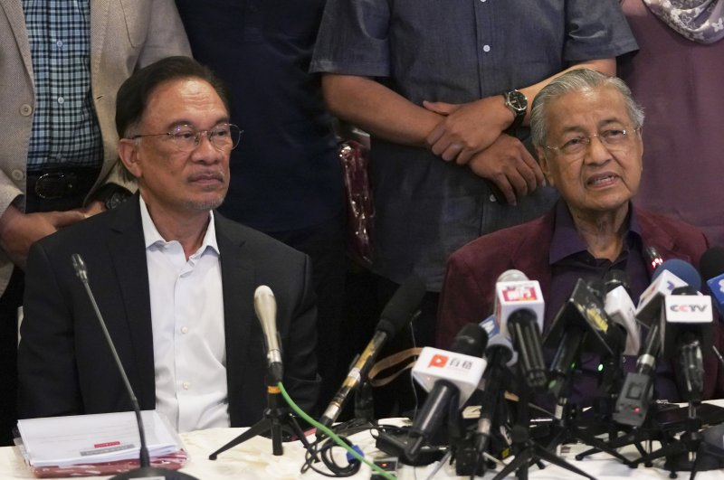In this Feb. 22, 2020, photo, Malaysian Prime Minister Mahathir Mohamad, right, talks to media next to his successor Anwar Ibrahim in Putrajaya, Malaysia. (AP Photo)