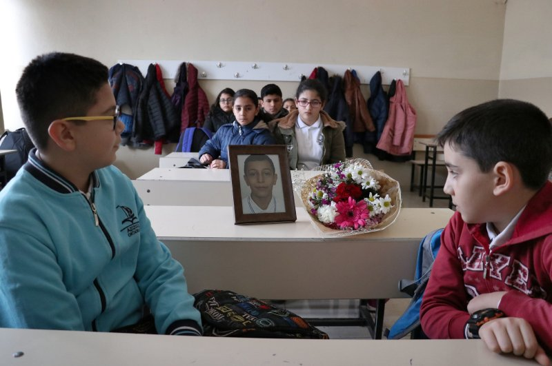 Classmates of Ömer Asaf Elidar, who died in the earthquake, look at his picture placed on his old desk, Elazığ, Feb. 24, 2020. (AA Photo)