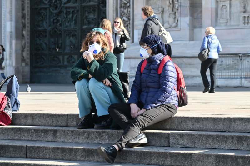 People wearing a respiratory mask sit on the steps of the churchyard of the Cathedral of the Duomo of Milan, Feb. 24, 2020. (AFP Photo)