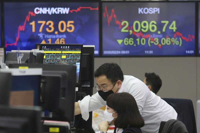 Currency traders wear face masks as they watch monitors at the foreign exchange dealing room of the KEB Hana Bank headquarters in Seoul, South Korea, Feb. 24, 2020. (AP Photo)
