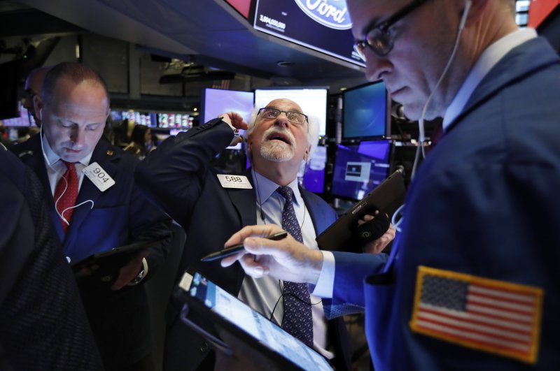 Traders Michael Urkonis, left, and Peter Tuchman, center, work on the floor of the New York Stock Exchange, Monday, Feb. 24, 2020. (AP Photo)