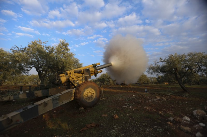 Turkish backed Syrian fighters fire a howitzer near the village of Neirab, in Idlib province, Syria, Monday, Feb. 24, 2020. (AP Photo)
