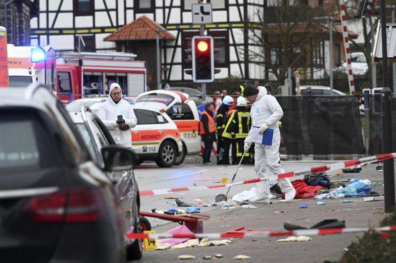 Police and rescue workers stand next to the scene of the accident with a car that is said to have crashed into a carnival parade in Volkmarsen, central Germany, Monday, Feb. 24, 2020. (AP Photo)
